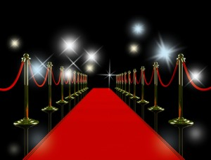 Red carpet event at night with lights flashing indicating paparazzi taking photographs