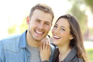 Front view of a couple posing outdoors with perfect smile and white teeth and looking at you in a park