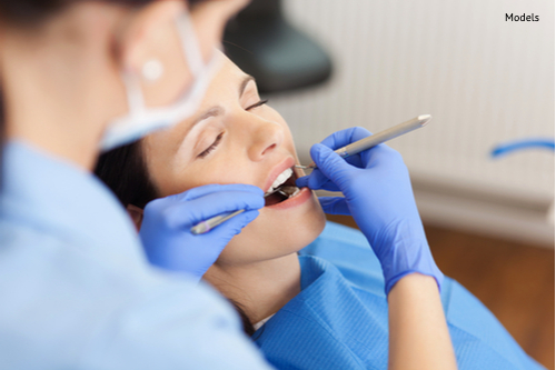 closeup of dentist examining mid adult patients mouth in clinic-img-blog