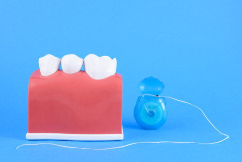 false mouth dentist in blue background with equipment for toothbrush and floss-img-blog