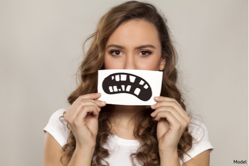 Brunette woman on grey background holding up a cartoon mouth representing tooth decay.