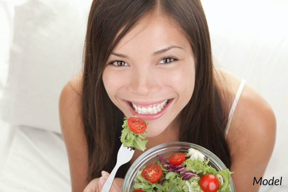 Young woman eating a salad to better the health of her teeth.